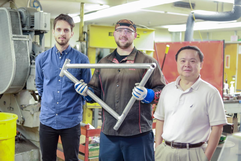 Graduate student Maximilian Sokoluk; laboratory mechanician Travis Widick, holding a demonstration bike frame welded using aluminum alloy 7075; and Professor Xiaochun Li.