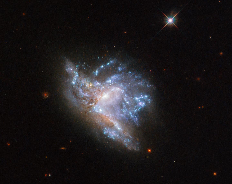 Hubble Uzay Teleskobu çarpışan iki galaksinin göz kamaştırıcı görüntüsünü belirledi…